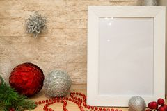 Silver and red christmas balls decoration, christmas mock up frame, silver snowflake, red beads and red winter berries with fir t. Ree branch on brick wall stock photography