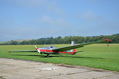 Silver and red glider stands on grass landing strip in small country airport while the weather is nice Royalty Free Stock Photos