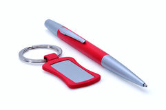 Silver-red metal pen and keychain isolated on white Stock Photography
