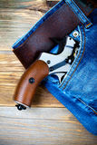 Silver revolver nagant with brown handle in the pocket Royalty Free Stock Photo