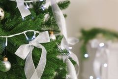 Silver ribbons and Christmas lights on fir tree in room. Closeup stock photos