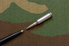 Silver rifle bullets against pen - a press freedom concept royalty free stock image