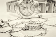 Silver ring and chain on the background of watches Stock Image