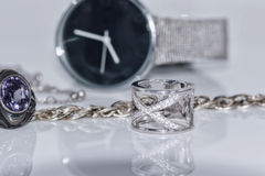Silver ring and chain on the background of watches Royalty Free Stock Photos