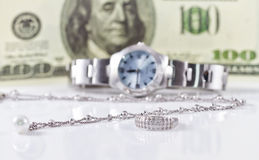 Silver ring and chain on the background of watches. Silver ring and chain on the background of women's watches and hundred dollars Stock Image