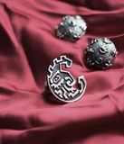 Silver ring and  earrings. Silver ring  and clip  earrings on the red silk Stock Image