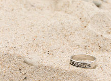 Silver ring lays on sand. Silver ring with ornament laying on a sandy beach Royalty Free Stock Photos