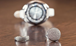 Silver rings and chain lying on background chrome watches Stock Photography