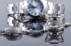 Silver rings and silver chain on the background of women's watch Stock Photos