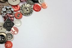 Silver and salmon pink buttons. A feminine collection of buttons with space for text along the right lower portion of the photograph Stock Images