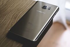 Silver Samsung Galaxy Smartphone on Top of Brown Wooden Table Royalty Free Stock Image