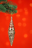 Silver Santa ornament. Silver Santa Christmas ornament hanging on a green pine tree branch against a red background Royalty Free Stock Images