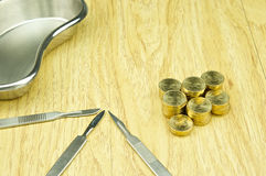Silver scalpel and pile of gold coins with emesis basin Royalty Free Stock Photo