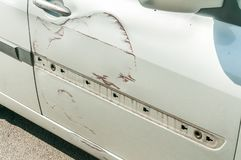 Silver scratched car with damaged door paint in crash accident or parking lot and dented damage of metal body from collision.  stock photography