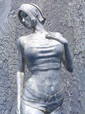 Silver sculpture of woman. Closeup of silver modern sculpture of young woman with decorative engraved background Stock Photo