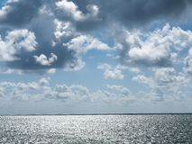 Silver sea bright clouds. Stock Photos