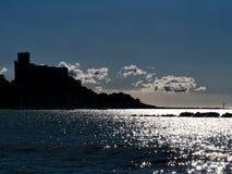 Silver sea at Lerici in Liguria, Italy. Popular tourist destinat. Beautiful back lit Lerici in winter. Mediterranean coast. Castle outline Royalty Free Stock Photo