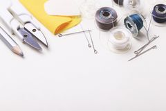 Sewing pins and plastic bobbin with color threads. Silver sewing pins, scissors, pencil, chalk and plastic bobbin with colour threads on white studio background Stock Photography