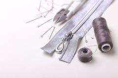 Sewing pins, scissors, zipper and plastic bobbin with colour thr. Silver sewing pins, scissors, zipper and plastic bobbin with colour threads on white studio Stock Photography