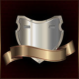 Silver shield and golden ribbon. Stock Photo