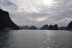 Silver shimmering sea with floating island silhouettes. At Ha Long Bay in Vietnam we find the beautiful silhouettes of soft rolling hills. Legend has it, the Stock Images