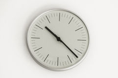 Silver shiny clock hanging at the wall Royalty Free Stock Image