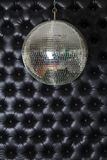 Silver shiny disco-ball on the black sofa background royalty free stock photos