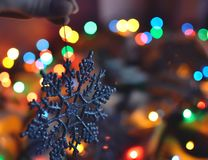 Silver shiny snowflake in the lights of a garland stock images