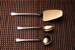 Silver shovel cake, teaspoon and spoon for sugar on the pattern table mat. Royalty Free Stock Photos