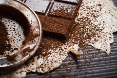 Silver sieve with cocoa dust on chocolate Stock Photos