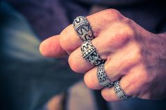 Silver signs with a medieval Scandinavian design on the fingers of a tight hand. Retro styled stock image