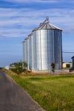 Silver silos in field Stock Photo