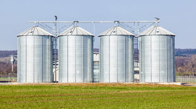 Silver silos in field Stock Image