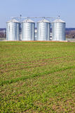 Silver silos in field Royalty Free Stock Photo