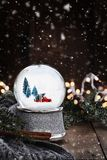 Silver Snow Globe with Old Pick Up Truck. Rustic image of a snow globe with old pick up tuck hauling a Christmas tree surrounded by pine branches, cinnamon royalty free stock photos