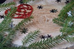 Silver snow, red heart and spruce branches on a wooden background Stock Photo