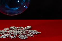 Silver snowflake and blue Christmas ball. On red and black background Stock Photos