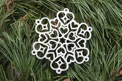 Silver snowflake ornament on green pine branches background. Winter christmas decoration lazer cut snowflake on pine branches stock image