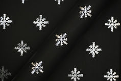Silver snowflakes on black paper stock photography