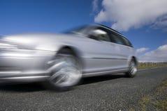 Silver speeding car. On mountain road Royalty Free Stock Photo
