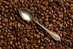 Silver spoon on coffee beans Stock Photos