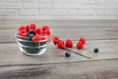 Silver spoon full of raspberries and blueberries, some spilled o. N gray wood desk, with out of focus bowl full of more berries on the side royalty free stock photography