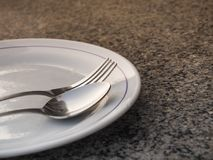 Silver spoon placed on a white plate Stock Photography
