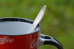 Silver spoon in red coffee mug on green background Stock Photo