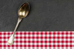 Silver spoon on a slate plate Royalty Free Stock Image