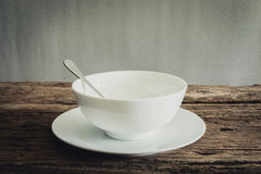 Silver spoon in white bowl and white plate on wooden tabletop Stock Photos