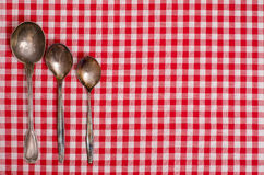 Silver spoons on a checkerd cloth Royalty Free Stock Photo