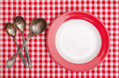 Silver spoons and red plate Stock Photography