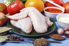 Silver spoons with spices and raw chicken wings on a wooden table. Fresh organic tomatoes for garnish.  royalty free stock photos