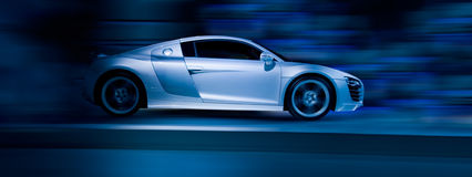 Silver sports car. Silver sportscar driving fast - side view Stock Photography
